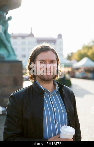 Portrait of businessman holding disposable coffee cup while standing at marketplace - Stock Photo