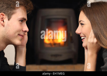 Side view of a couple flirting and looking each other in front a fireplace - Stock Photo