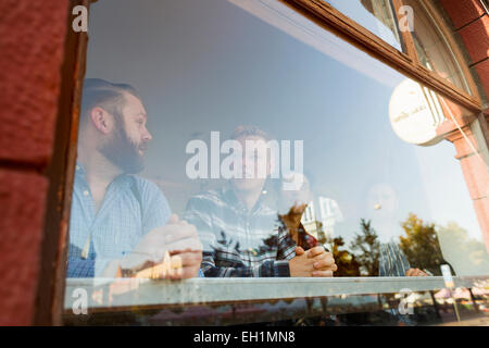Businessmen communicating in cafe seen through glass window - Stock Photo