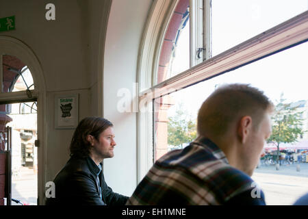 Thoughtful businessman looking through window at cafe - Stock Photo