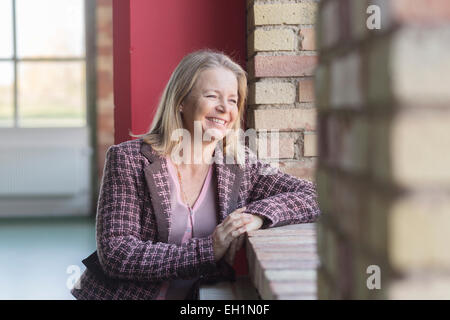 Happy mature woman leaning on window sill in gym - Stock Photo
