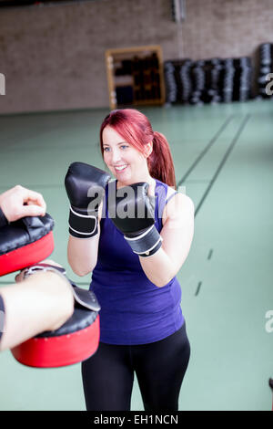 Young woman with trainer practicing boxing in health club - Stock Photo