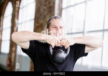 Smiling young man lifting kittlebell in health club - Stock Photo