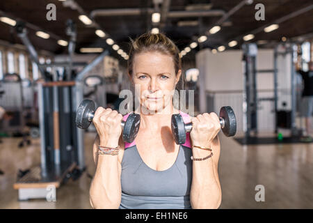 Portrait of confident mature woman lifting dumbbells in health club - Stock Photo