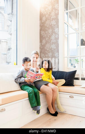 Full length of children listening mother reading story book in living room - Stock Photo