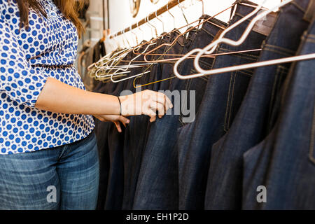 Midsection of woman choosing jeans in factory - Stock Photo