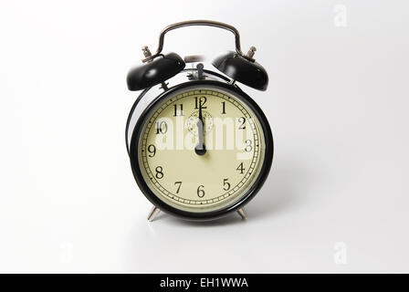 Old fashion alarm clock ringing at twelve o`clock - Stock Photo