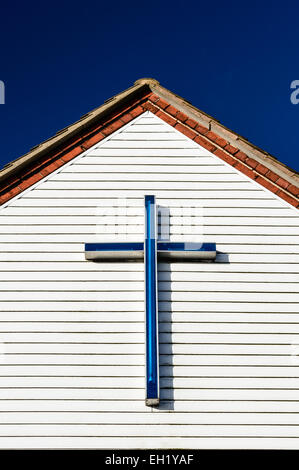 A blue cross/crucifix atop the eave of  St Wilfrid's Parish Hall in Kirkby In Ashfield, Nottinghamshire, England - Stock Photo