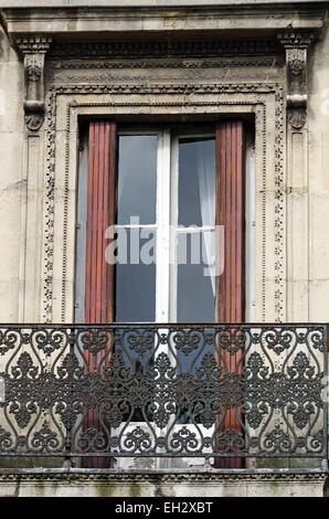 Tall French doors open onto a wrought iron balcony in the Marais, Paris, France. - Stock Photo