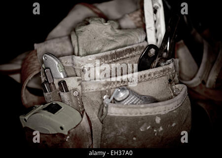 Closeup of rugged carpenters leather work bags and belt with used construction tools isolated on black background - Stock Photo