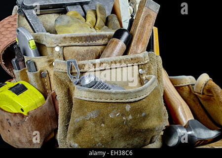 Rugged worn carpenters leather work bags and belt with construction tools and hammer isolated on black and selective - Stock Photo