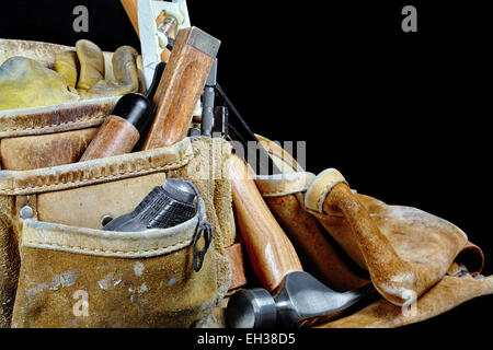 Rugged worn carpenters leather work bags and belt with construction tools and hammer isolated on black - Stock Photo
