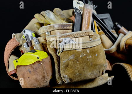 Rugged worn carpenters leather work bags and belt with vintage construction tools and hammer isolated on black. - Stock Photo