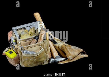 Rugged worn carpenters leather work bags and belt with used construction tools and hammer isolated on black background - Stock Photo