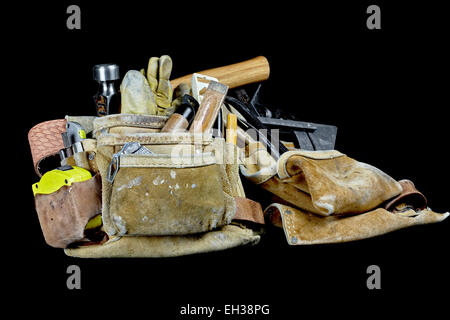 Rugged worn carpenters leather work bags and belt with used construction tools isolated on black background - Stock Photo