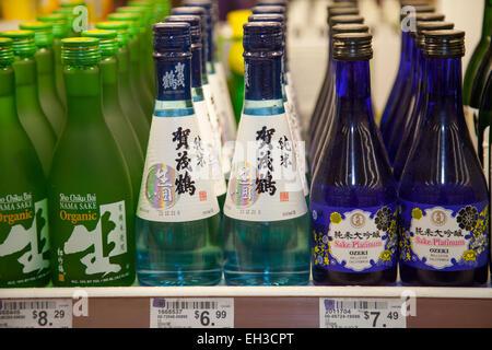 Sake wine bottles on the shelf in an Asian market, Richmond, California, USA. - Stock Photo