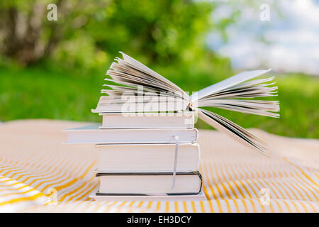 pile of books with one opened book on nature background - Stock Photo