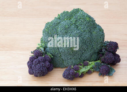 Green and purple sprouting  broccoli on a pale wooden board. - Stock Photo