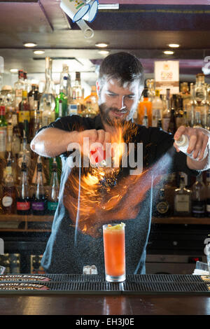 A male barman, bar tender, mixologist makes a fantastic cocktail in a high end restaurant / bar / public house - Stock Photo