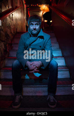 a bar owner sits on some steps in his pub in Brighton lit by blue light - Stock Photo