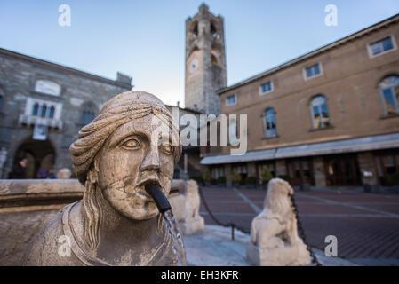 The Contarini fountain in the central square Piazza Vecchia in Bergamo, Italy. On the background, the Palazzo del - Stock Photo