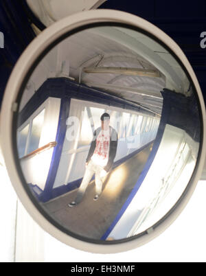 man walking past convex safety mirror above steps on pedestrian walkway at railway station selby united kingdom - Stock Photo