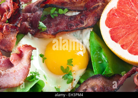 Fried egg with bacon, lettuce and grapefruit. - Stock Photo