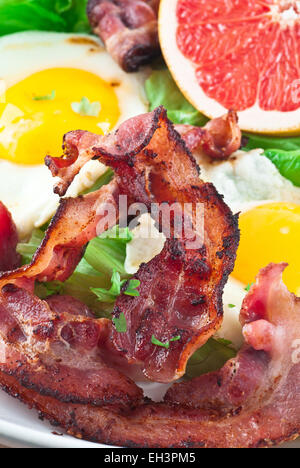 Bacon with fried eggs, lettuce and grapefruit. - Stock Photo