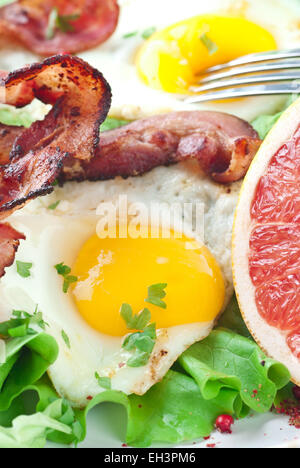 Fried egg and bacon, lettuce and grapefruit. - Stock Photo
