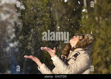 Happy girl throwing snow in the air on winter holdays in a forest in a sunny day - Stock Photo