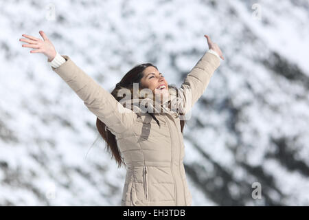 Happy woman raising arms on winter holidays with a snowy mountain in the background - Stock Photo