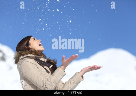 Happy woman throwing snow in the air on winter holdays with a snowy mountain and a blue sky in the background - Stock Photo