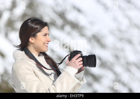 Tourist woman photographing on winter holidays with a snowy mountain in the background - Stock Photo