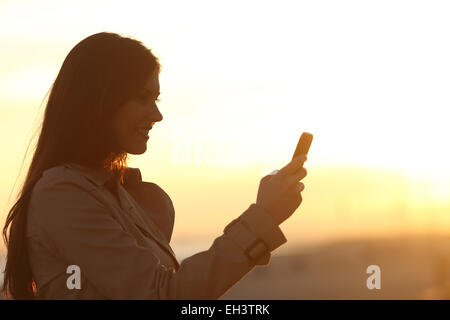 Side view of a happy woman silhouette using a smart phone at sunset - Stock Photo