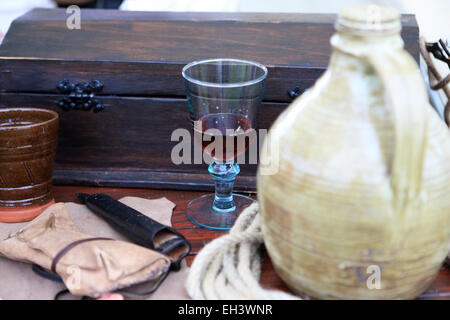 Items at at re-enactment - wooden chest, wine jug and goblet, rope and pouch - Stock Photo