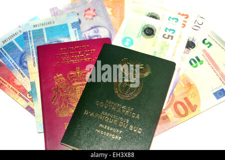 Image of South African and British Passports full of money photographed in a studio against a white background. - Stock Photo