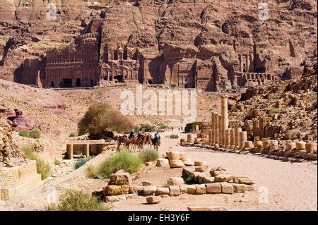 PETRA,  JORDAN - OCT 12, 2014: Roman pillars on colonnaded street, and the 'Royal tombs' on the background in the - Stock Photo