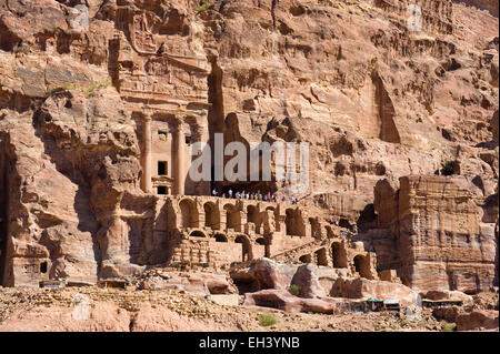 PETRA,  JORDAN - OCT 12, 2014: Tourists are walking in front of the 'Urn Tomb' one of the 'Royal Tombs' in Petra - Stock Photo