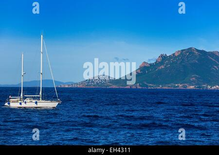 France, Alpes Maritimes, sailboat off the Lerins Islands and the Esterel Mountains in the background - Stock Photo