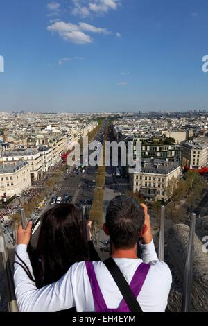 France, Paris, tourist couple looking at the Champs Elysees from the Arc de Triomphe Etoile - Stock Photo