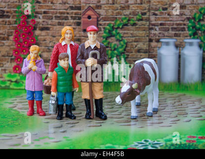 Toy farming family - Mum, Dad, son and daughter with one of their cows. - Stock Photo