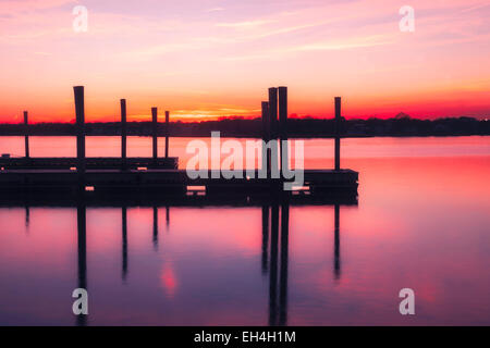 Silhouette of a empty dock on the water, under a calming pink and orange sky at sunset. - Stock Photo