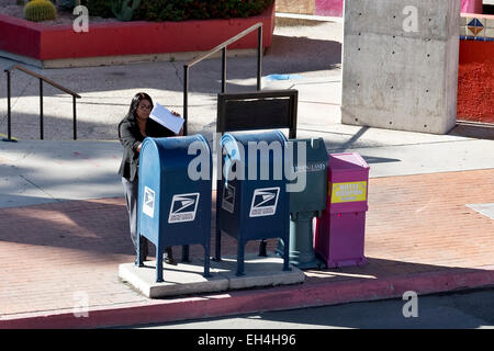 Woman mailing documents via public USPS mailbox - Stock Photo