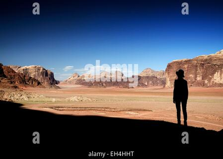 Jordan, Wadi Rum desert, protected area listed as World Heritage by UNESCO, silhouette of a woman and red sand desert - Stock Photo