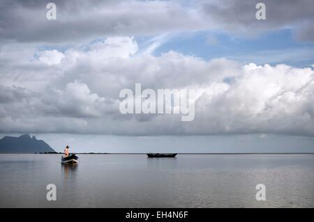 Malaysia, Borneo, Sarawak, Bako National Park, fisherman on a boat on the South China sea, cloudy sky - Stock Photo