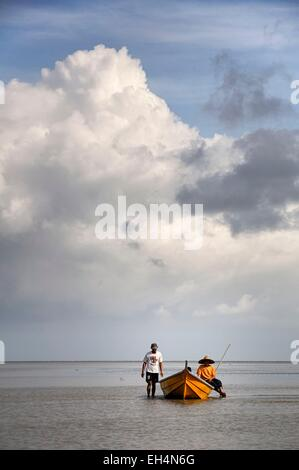 Malaysia, Borneo, Sarawak, Bako National Park, fishermen on a boat on the South China sea at low tide, cloudy sky - Stock Photo