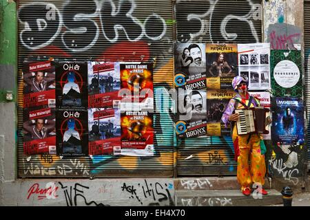 Turkey, Istanbul, SIraselviler Caddesi, street performer dressed as clowm playing the accordion in front of posters - Stock Photo