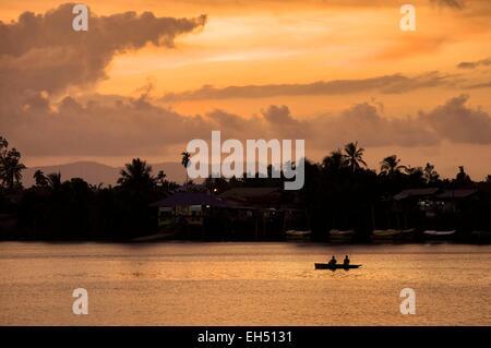 Malaysia, Borneo, Sarawak, Kuching, silhouette of fishermen on a boat on Sungai Sarawak river at sunset - Stock Photo