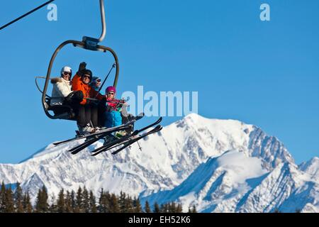 France, Savoy, Les Saisies ski resort, chairlift and skiers in front Mont Blanc - Stock Photo