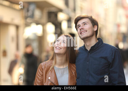 Couple walking and looking above in the street of a city - Stock Photo